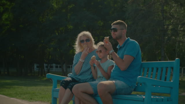Multi-generation-family-eating-ice-creams-on-bench
