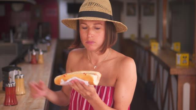 Modern-woman-in-straw-hat-enjoying-tasty-hotdog