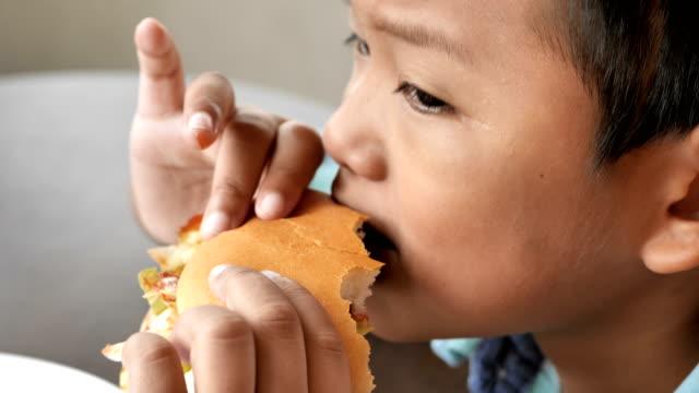 Niedlichen-asiatischen-jungen-freuen-uns-einen-Hamburger-Essen-im-Restaurant-4k-Video-Zeitlupe