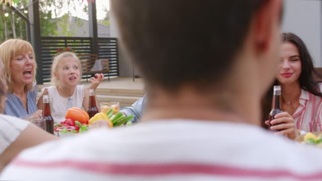 Gran-familia-jardín-fiesta-celebración-reunidos-juntos-en-la-mesa-de-familiares-y-amigos-jóvenes-y-ancianos-son-comer-beber-pasando-por-platos-Joking-y-divierte-