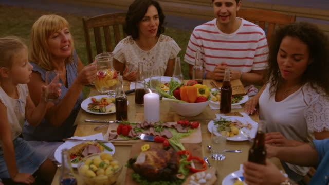 Grupo-de-amigos-se-reunieron-juntos-en-la-mesa-de-familiares-y-amigos-jóvenes-y-ancianos-son-comer-beber-pasando-por-platos-Joking-y-divierte-Celebración-de-noche-de-fiesta-jardín-