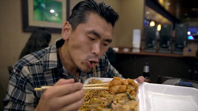 slow-motion-tattooed-asian-man-eating-and-devouring-chinese-takeout-food