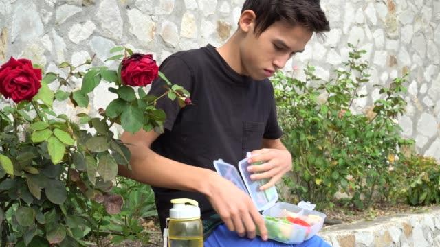Adolescente-comiendo-al-aire-libre-de-comida-casera-y-sana