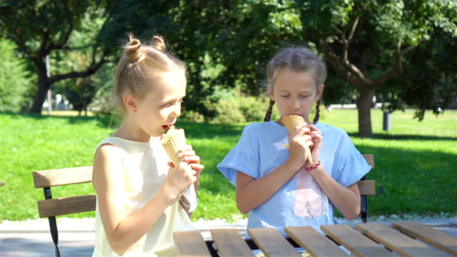 Little-girls-eating-ice-cream-outdoors-at-summer-in-outdoor-cafe