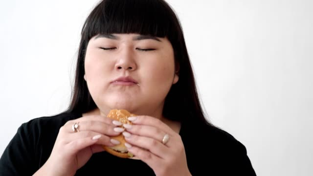the-girl-of-Asian-appearance-eats-a-Burger-and-enjoys-the-taste-not-a-healthy-diet-for-young-people