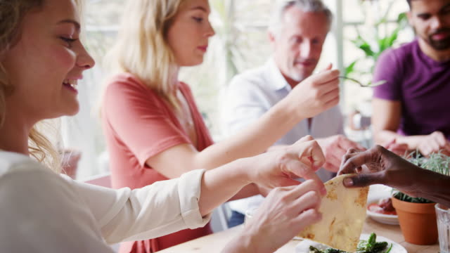A-mixed-age-group-of-adult-friends-sharing-tapas-at-a-table-in-a-restaurant-selective-focus-focus-on-foreground