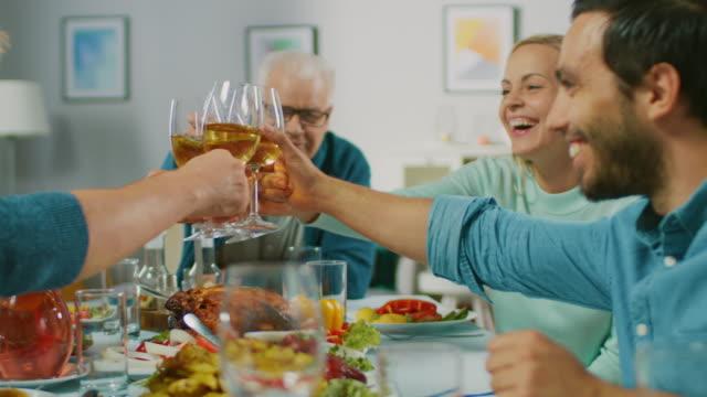 Gran-familia-y-fiesta-de-amigos-en-casa-grupo-diverso-de-personas-se-reunieron-en-la-mesa-Comer-beber-hacer-tostadas-y-divertirse-Fiesta-durante-el-día-