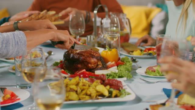 Disparo-de-la-cámara-de-Close-up:-Gran-familia-y-amigos-la-celebración-en-casa-grupo-diverso-de-jóvenes-y-viejos-compartir-comidas-tallan-Turquía-pasan-platos-comen-alimentos-y-bebidas-