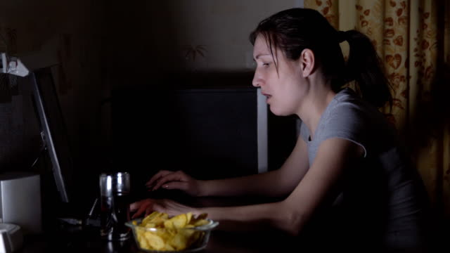 Junge-Frau-am-Computer-sitzen-und-Essen-chips