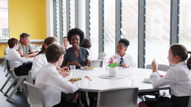 Lehrerin-mit-Gruppe-von-Schülerinnen-und-Schüler-tragen-einheitliche-an-Tisch-sitzen-und-Essen-In-der-Cafeteria