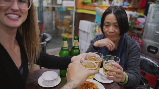 diverse-group-of-travels-make-a-cheers-over-dinner-at-a-Hong-Kong-restaurant