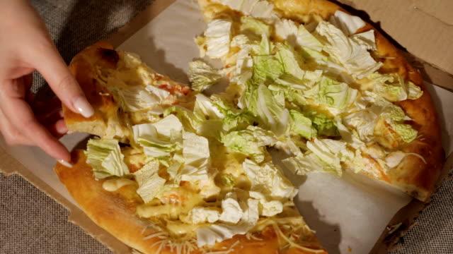 Una-rebanada-de-pizza-en-la-mano-
