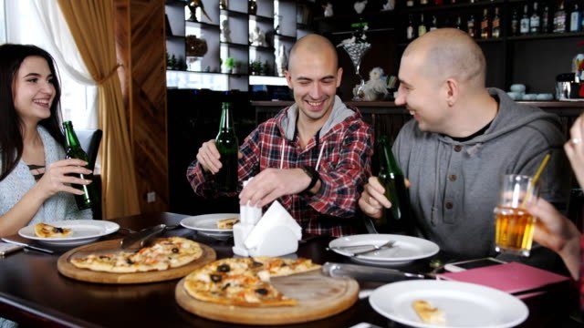 Company-of-cheerful-friends-at-the-table-of-the-restaurant-eating-pizza-drinking-beer-and-having-fun-together-