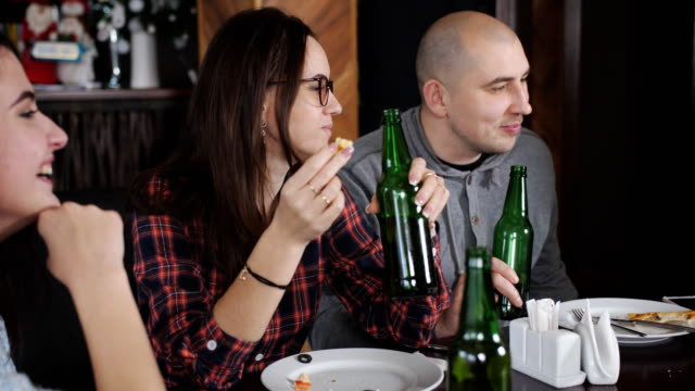 Fun-in-the-restaurant-eating-pizza-and-drinking-beer-Two-guys-and-two-girls-in-the-pizzeria-