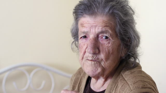 Unhealthy-old-woman-eating-looking-camera-at-home
