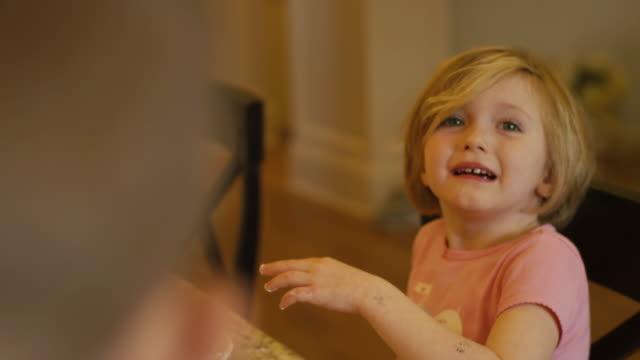 Una-niña-jugando-con-sus-tortitas-con-las-manos-hablando-y-sonriendo