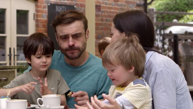Familie-Sitzt-Am-Café-Tisch-Im-Freien-Und-Hat-Einen-Snack-Auf-R3d