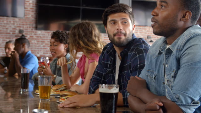 Group-Of-Friends-Watching-Game-In-Sports-Bar-On-Screens