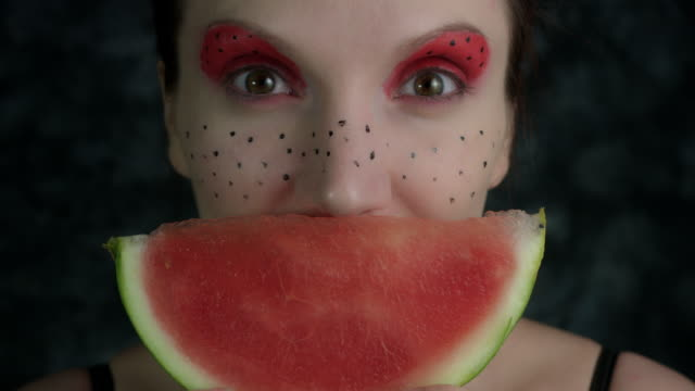4k-Shot-of-a-Woman-with-Multicoloured-Make-up-with-Watermelon