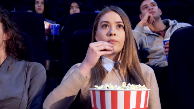 Girl-slowly-puts-the-popcorn-in-her-mouth-at-the-movie-theater