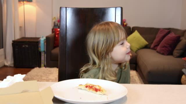 niño-riendo-en-casa-y-comer-pizza