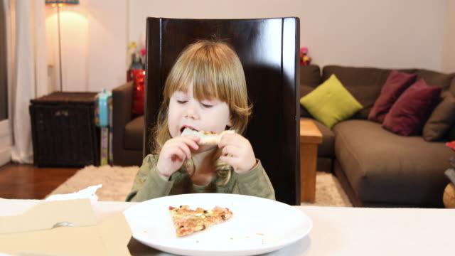 sonriente-niño-comiendo-pizza-en-casa