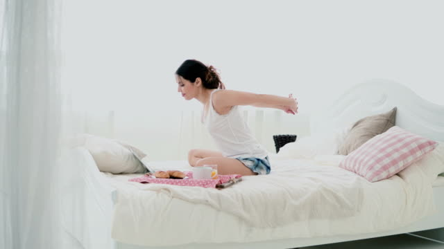 Young-brunette-woman-stretches-on-a-bed-Beautiful-girl-using-laptop-during-breakfast-Drinking-juice-and-dancing
