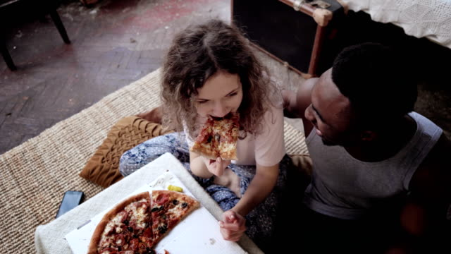 Woman-offers-pizza-to-man-but-eat-slice-by-herself-Multiracial-couple-having-fun-during-the-meal-with-fast-food