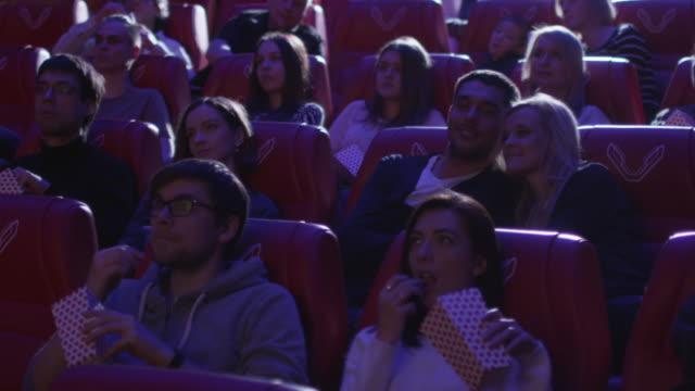 Joven-pareja-romántica-es-elaborar-y-besos-mientras-ve-una-proyección-de-la-película-en-un-cine-de-película-