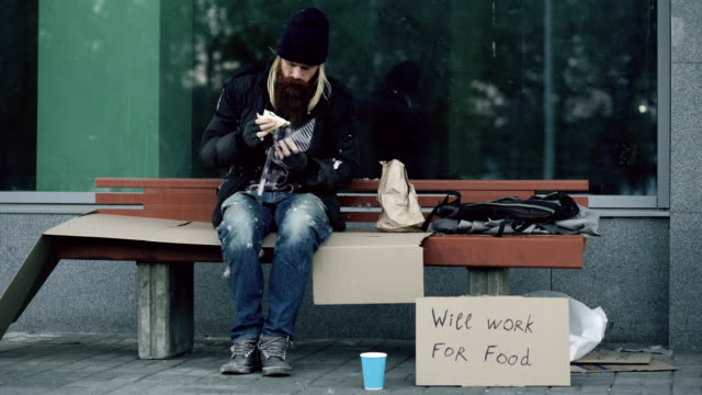Homeless-and-jobless-american-man-with-cardboard-sign-eat-sandwich-on-bench-at-city-street-because-of-immigrants-crisis-in-usa
