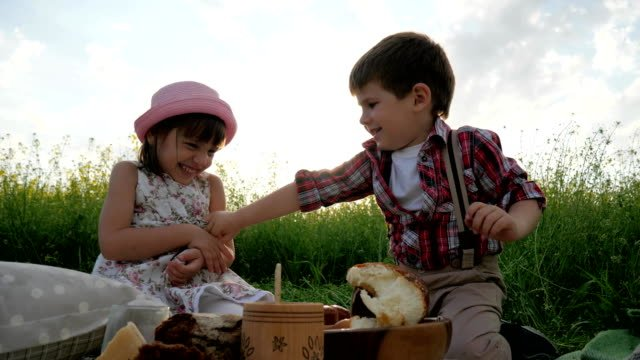 Children-having-fun-in-fresh-air-kid-at-picnic-family-resting-in-nature-friends-laugh-happily-good-mood-healthy-food-for-healthy-child
