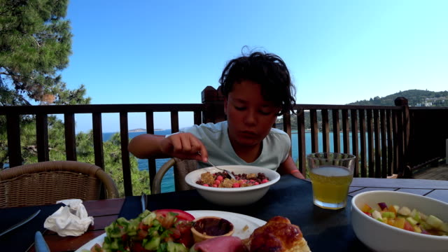 Handsome-preteen-eating-breakfast-at-the-outdoor
