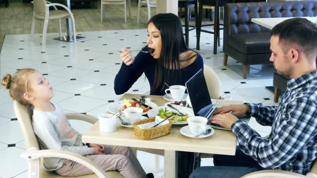 Tiempo-libre-de-jóvenes-familia-en-café-Madre-solícita-pide-dauhter-poco-caprichoso-para-comer-verduras-Mientras-tanto-padre-está-ocupado-con-el-ordenador-portátil
