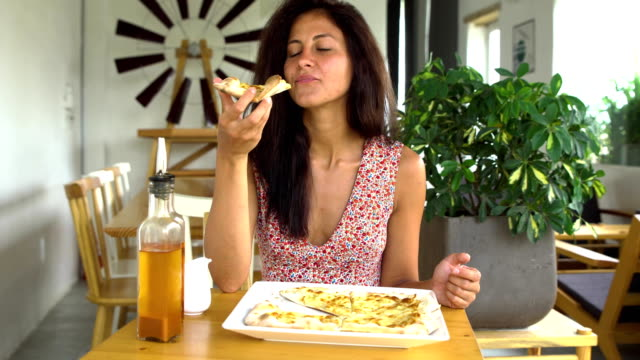 Woman-eating-cheese-pizza-slice