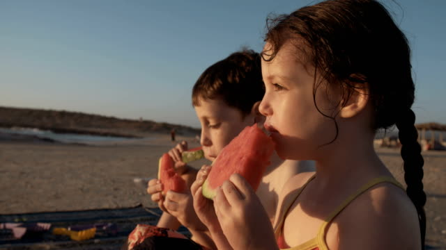 Three-kids-eating-watermelons-at-the-beach