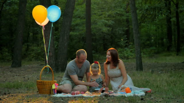 Beautiful-family-relaxing-on-picnic-in-the-forest