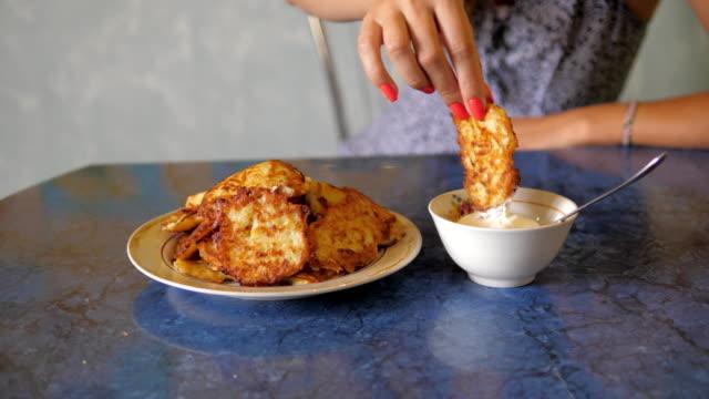 Joven-toma-frito-delicioso-panqueque-vegetal-sumergido-en-salsa-y-comer