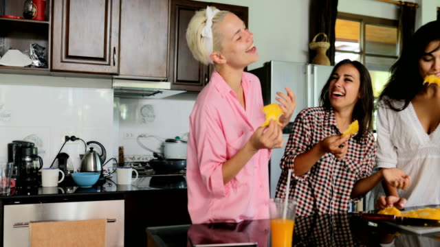 Girls-Group-Eating-Delicious-Tropical-Fruit-On-Breakfast-Talking-In-Kitchen-Studio-Modern-House-Interior