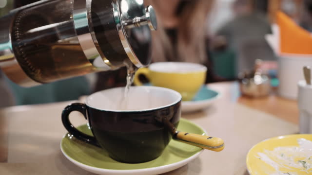 An-unrecognizable-woman-pours-tea-using-a-Frenchpress-in-a-cup-at-a-restaurant