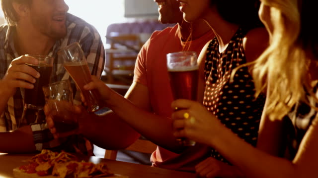 Friends-interacting-with-each-other-while-having-glass-of-beer-4k