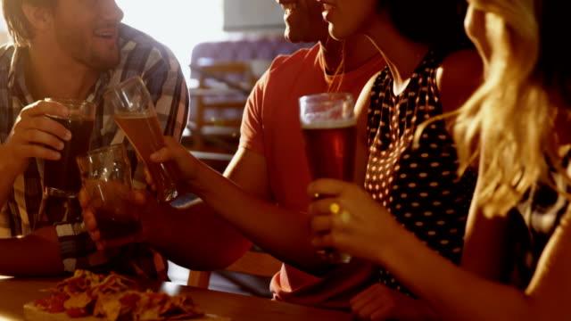 Freunde-die-miteinander-interagieren-bei-Glas-Bier-4k