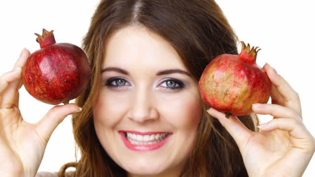 Cheerful-woman-holds-pomegranate-fruits-isolated
