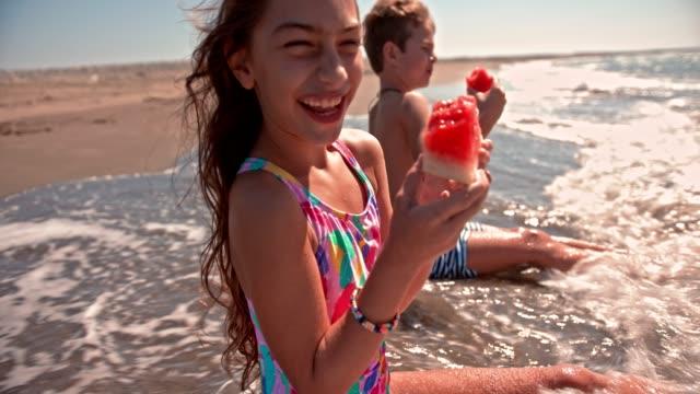 Niño-y-niña-comiendo-Sandia-en-la-playa