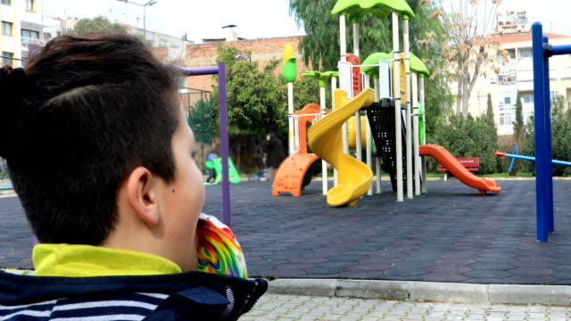 child-eating-lollipop-at-the-playground