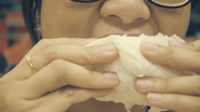 cerrar-tiro:-mujer-asiática-comiendo-un-bollo-del-vapor