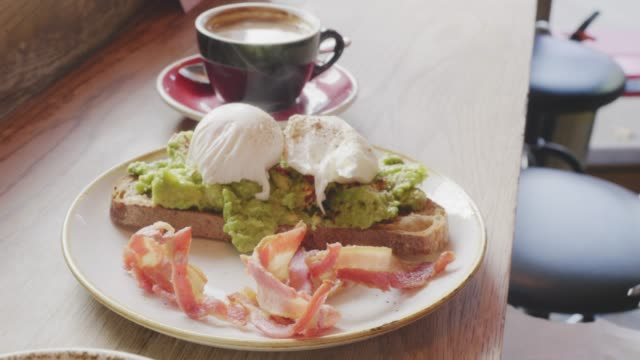 Woman-Squeezing-Lemon-Over-Poached-Egg-And-Avocado-On-Toast