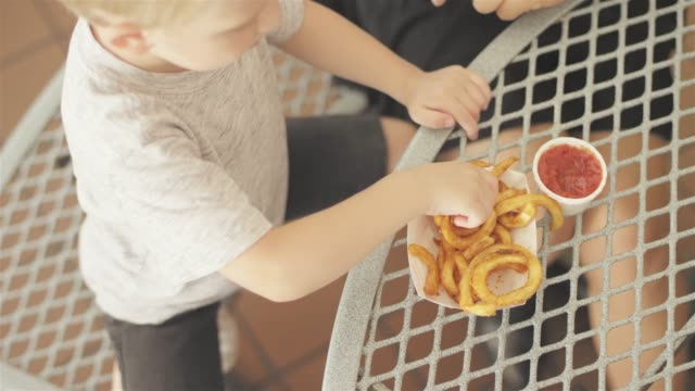 Downward-shot-of-a-little-kid-dipping-his-curly-fry-in-ketchup-and-eats-it-at-an-outdoor-food-court