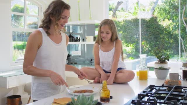 Madre-e-hija-comiendo-panqueques-en-casa-cocina