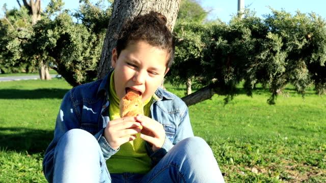 Joven-comer-croissant-en-el-exterior