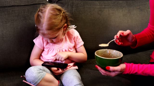 A-little-girl-looks-at-her-smartphone-while-her-mother-feeds-her-a-spoon